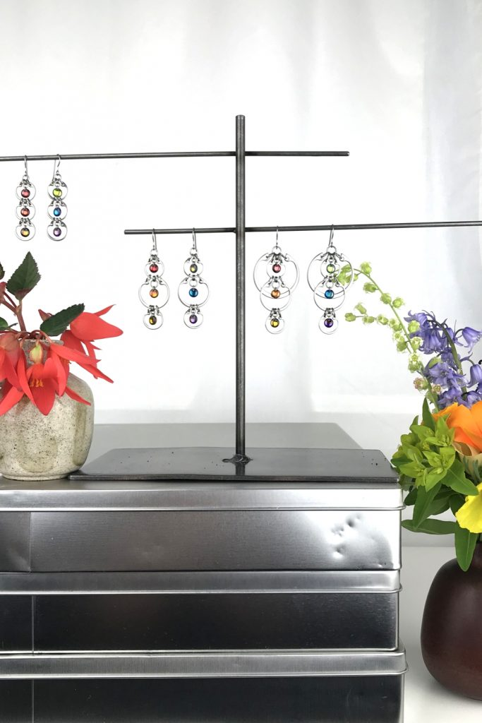A ceramic bud vase of red begonia flowers sits on a stack of metal boxes, next to a jewelry stand with Wraptillion's modern Tripled Rainbow Earrings, Alternating Rainbow Earrings, and Cascading Rainbow Earrings. Another ceramic bud vase with bluebells, poppies, fringe flowers, and euphorbia sits nearby in a studio.
