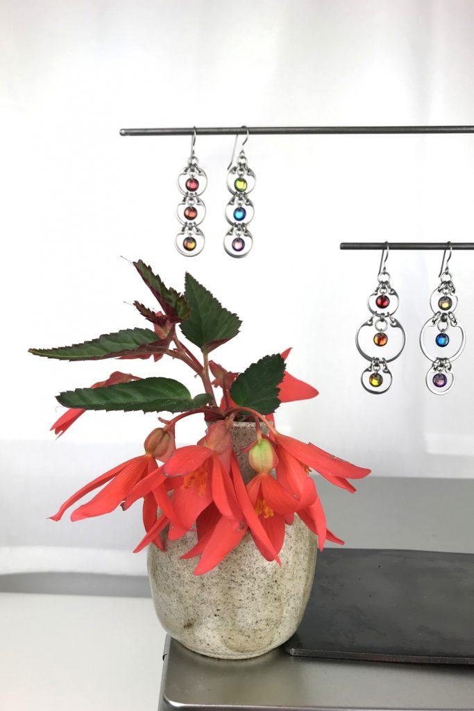 A ceramic bud vase of red begonia flowers sits on a metal box, next to a jewelry stand with Wraptillion's modern Tripled Rainbow Earrings and Alternating Rainbow Earrings, in a studio.