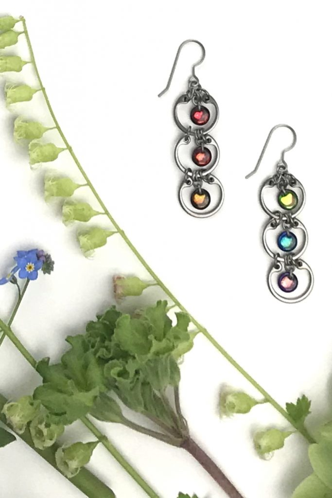 Wraptillion's modern Tripled Rainbow Earrings in a flatlay next to green fringe flowers and primroses and blue forget-me-nots.