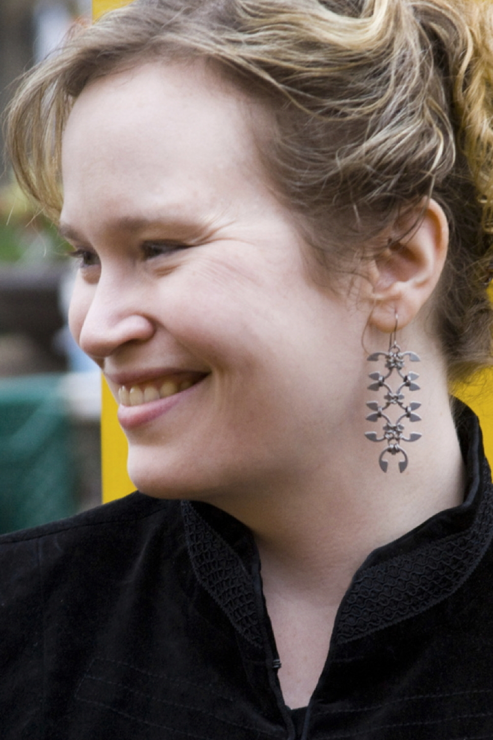 Smiling model wears Wraptillion's Long Wisteria Earrings with blonde curly hair in an updo and a black velvet jacket.