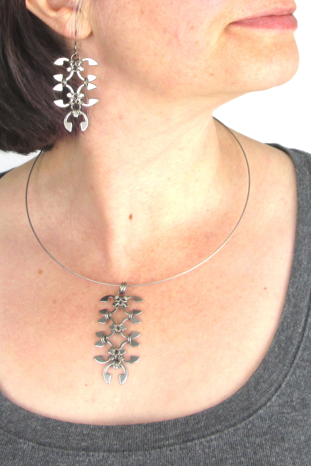 Close cropped modeled image of Wraptillion's Short Wisteria Earrings and Wisteria pendant, with a scoop neck gray tee.