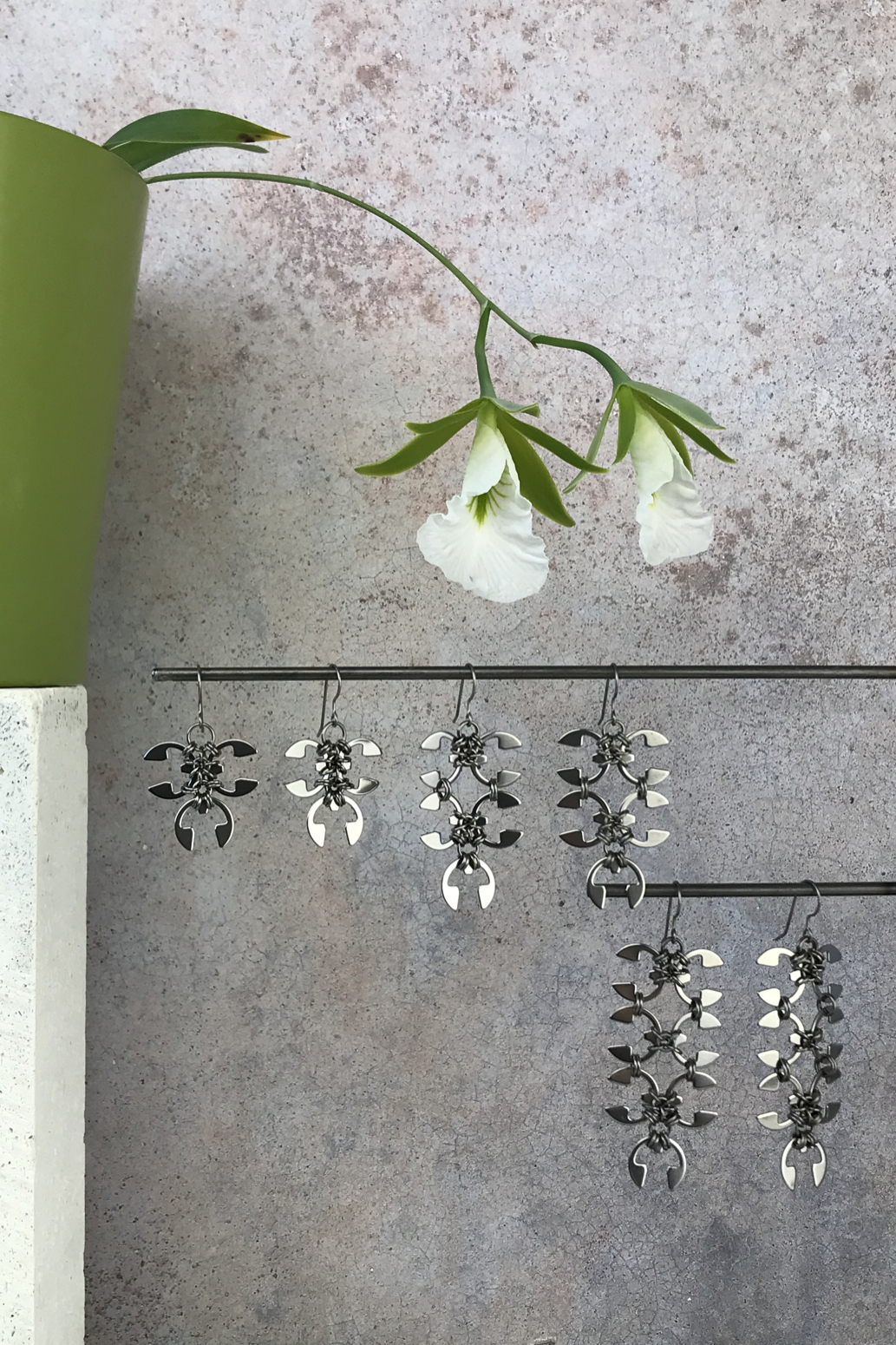 Wraptillion's Ivy Earrings, Short Wisteria Earrings, and Long Wisteria Earrings with blooming Encyclia mariae in front of a textured gray wall.