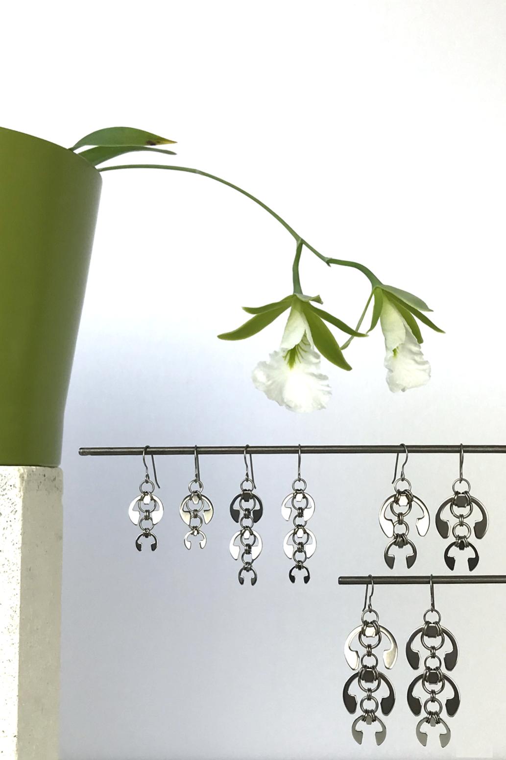 Wraptillion's Short Fuchsia Earrings, Long Fuchsia Earrings, Hops Earrings, and Laburnum Earrings with blooming orchid Encyclia mariae.