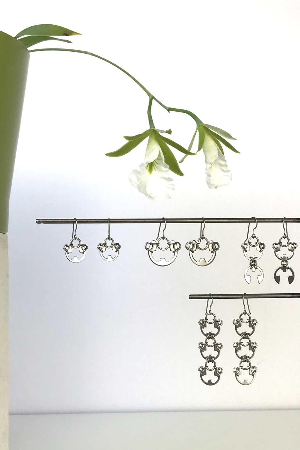 Wraptillion's Small Poppy Earrings, Large Poppy Earrings, Scarab Earrings, and Lotus Earrings with blooming orchid Encyclia mariae.