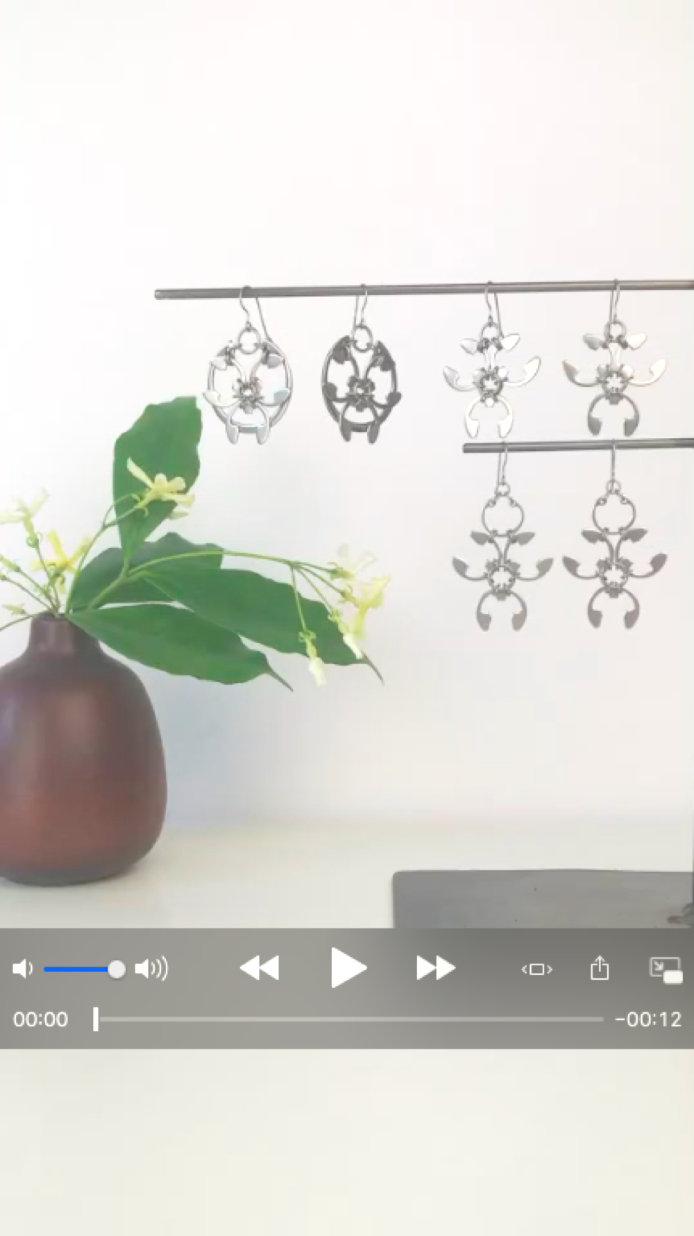 Cover screen for a short video featuring pale yellow star jasmine (Trachelospermum asiaticum) flowers and green leaves in a bud vase by Heath Ceramics on a desk in Wraptillion's studio workspace, with the modern botanical-inspired Rose Window Earrings, Trellis Earrings, and Garland Earrings.