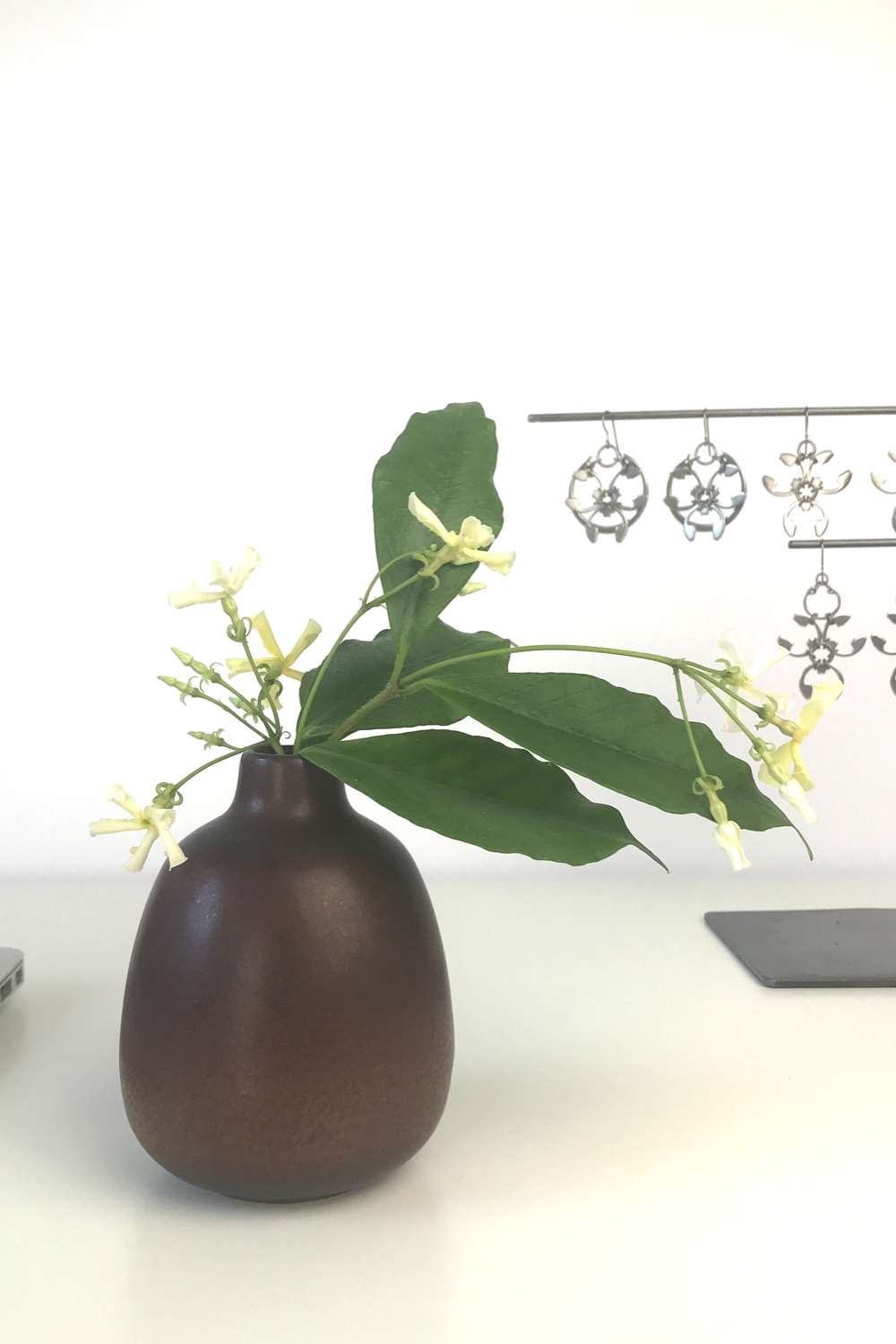 Pale yellow star jasmine (Trachelospermum asiaticum) flowers and green leaves in a bud vase by Heath Ceramics on a desk in Wraptillion's studio workspace, with the modern botanical-inspired Rose Window Earrings, Trellis Earrings, and Garland Earrings.