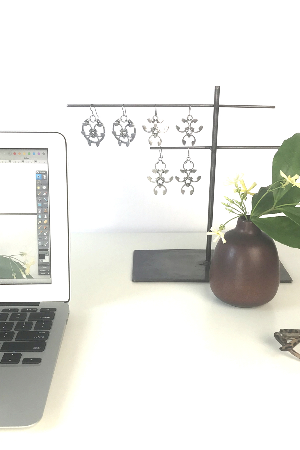 Pale yellow star jasmine (Trachelospermum asiaticum) flowers and green leaves in a bud vase by Heath Ceramics on a desk in Wraptillion's studio workspace, with the modern botanical-inspired Rose Window Earrings, Trellis Earrings, and Garland Earrings, reading glasses, and an open laptop..