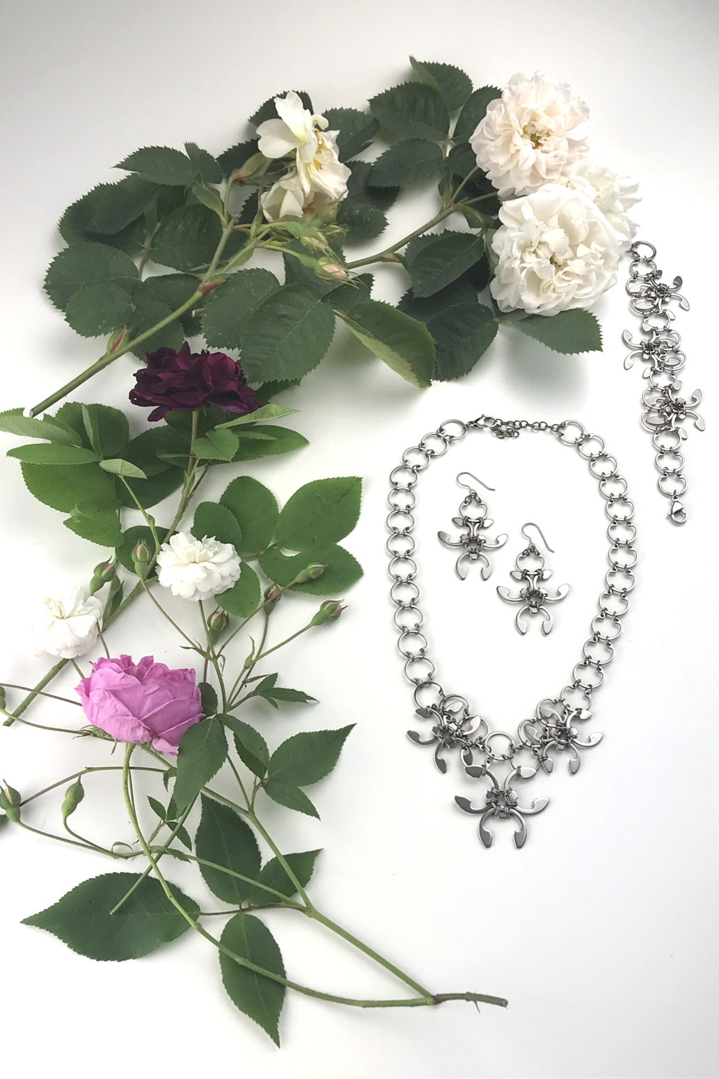 Flatlay of old roses (Rosa alba, Rosa gallica officinalis, moss rose 'Capitaine John Ingram', & 'Felicite et Perpetue') with the Garland Necklace, Garland Earrings, and Garland Bracelet in Wraptillion's studio.