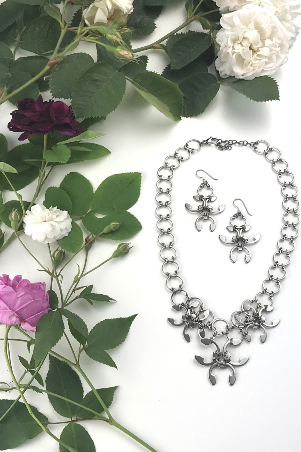 Cropped flatlay of old roses (Rosa alba, Rosa gallica officinalis, moss rose 'Capitaine John Ingram', & 'Felicite et Perpetue') with the Garland Necklace and Garland Earrings in Wraptillion's studio.