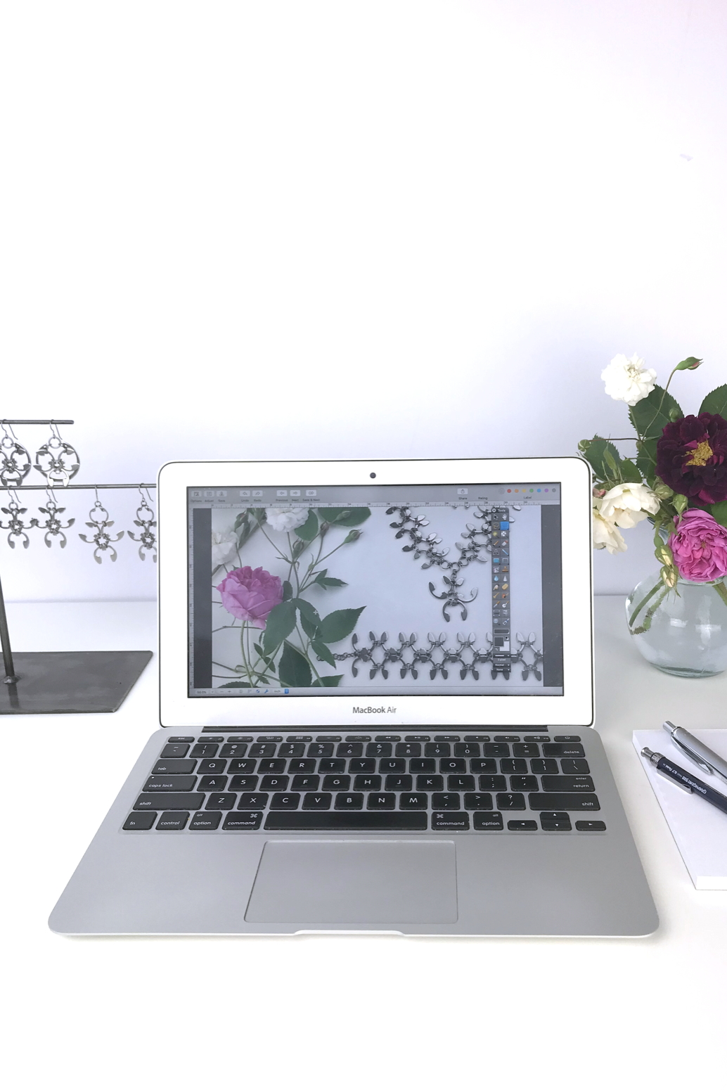 Open laptop next to a small arrangement of old roses (Rosa alba, Rosa gallica officinalis, moss rose 'Capitaine John Ingram', & 'Felicite et Perpetue') with earrings from the Mechanical Garden collection in Wraptillion's studio.