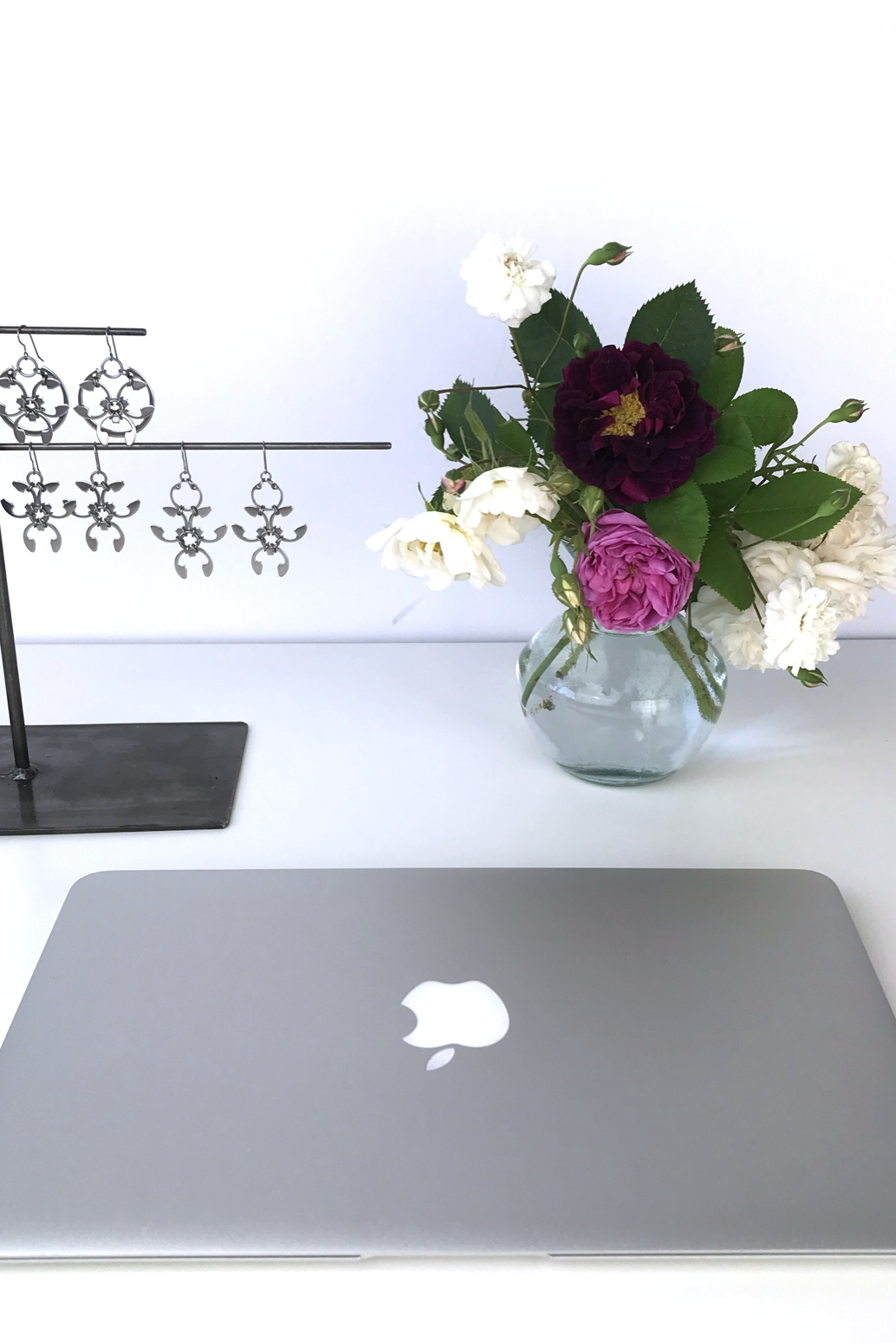 Closed laptop next to a small arrangement of old roses (Rosa alba, Rosa gallica officinalis, moss rose 'Capitaine John Ingram', & 'Felicite et Perpetue') with earrings from the Mechanical Garden collection in Wraptillion's studio.