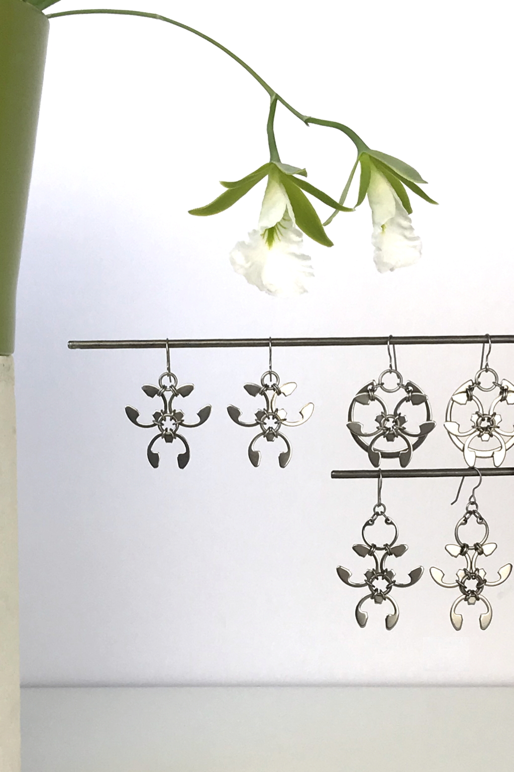 Wraptillion's Trellis Earrings, Rose Window Earrings, and Garland Earrings with blooming orchid Encyclia mariae.