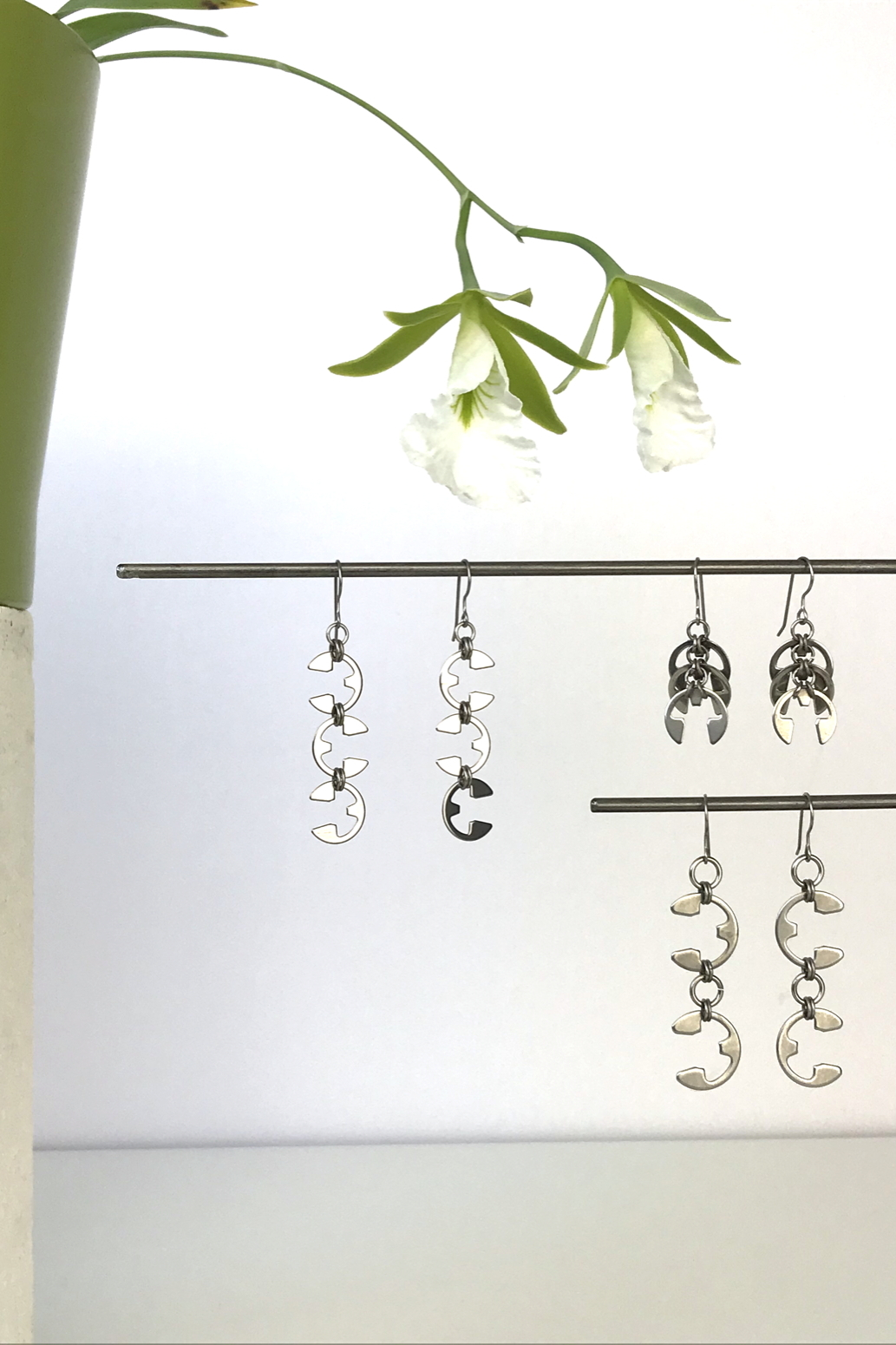 Wraptillion's Vine Earrings, Fir Cones Earrings, and Tendril Earrings with blooming orchid Encyclia mariae.