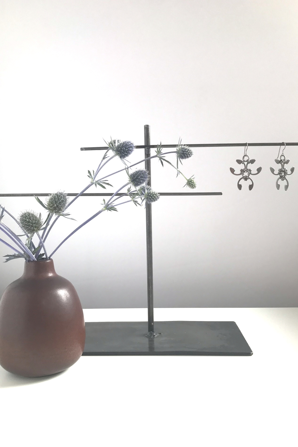 Sea holly (Eryngium) in a brown bud vase by Heath Ceramics on a desk next to a jewelry stand with Wraptillion's spiky floral Trellis Earrings.