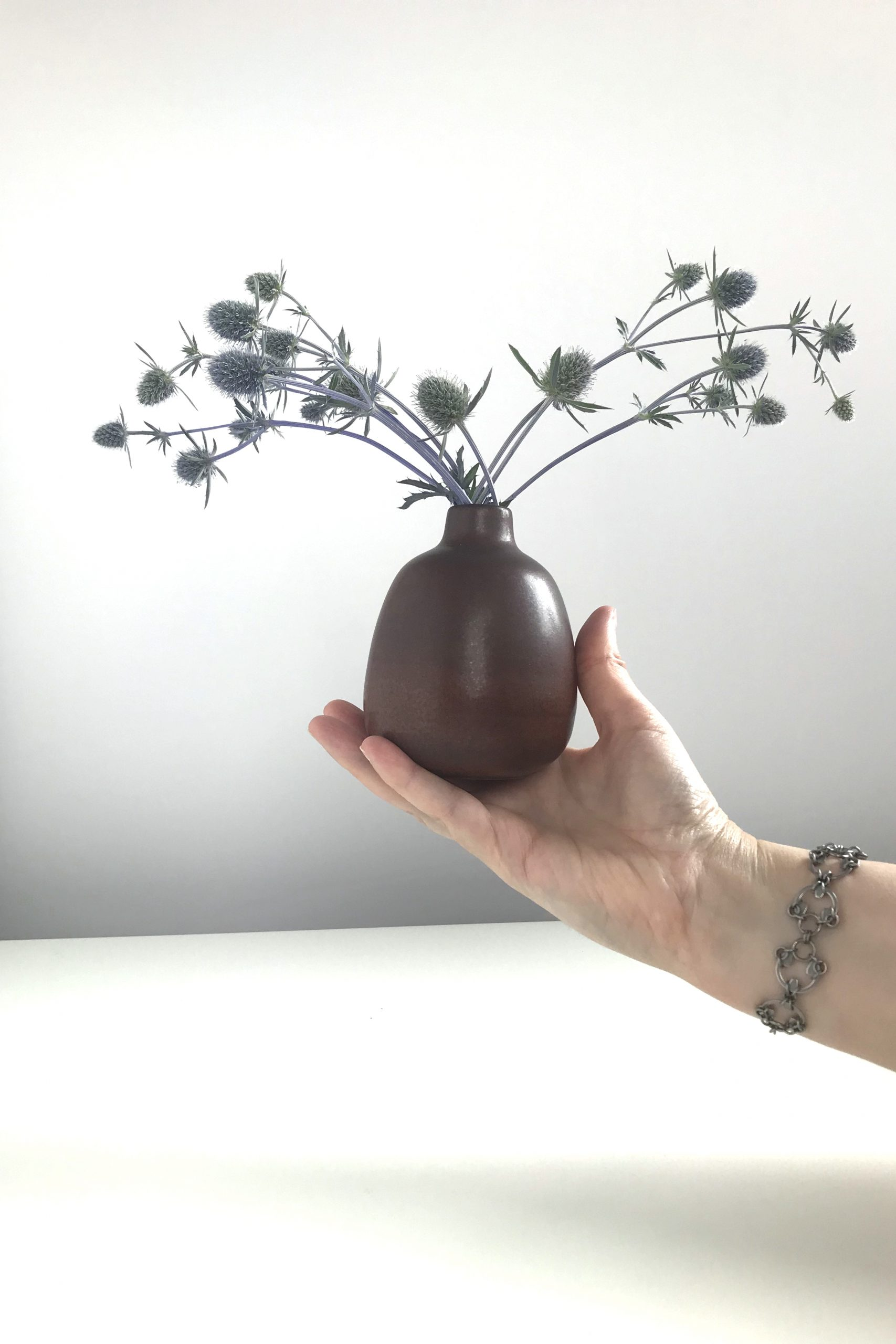 A hand holding a brown bud Heath Ceramics bud vase of sea holly (Eryngium), wearing Wraptillion's intricate modern chainmaille Scarab Bracelet..