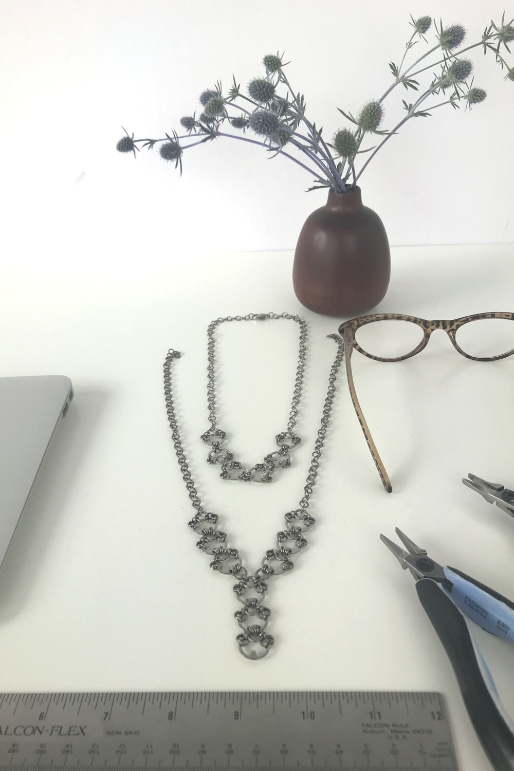 Sea holly (Eryngium) in a brown bud vase by Heath Ceramics on a desk next to Wraptillion's Delicate Scarab Necklace, Delicate Lotus Necklace, reading glasses, ruler, pliers, and a laptop.