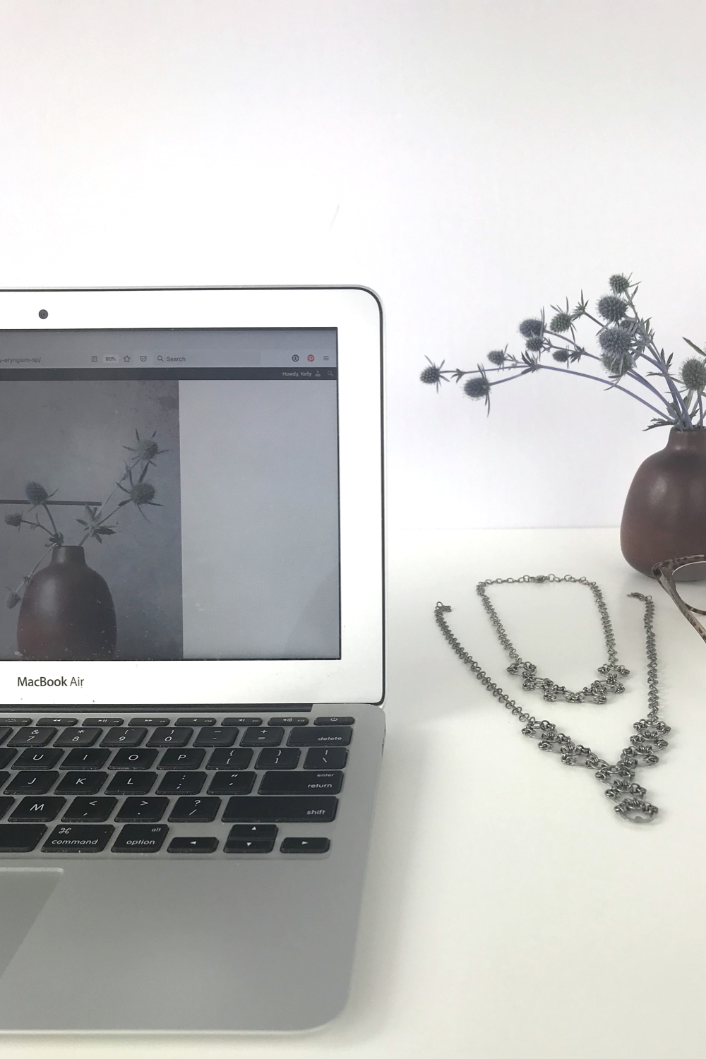 Sea holly (Eryngium) in a brown bud vase by Heath Ceramics on a desk next to Wraptillion's Delicate Scarab Necklace, Delicate Lotus Necklace, reading glasses, and a laptop.