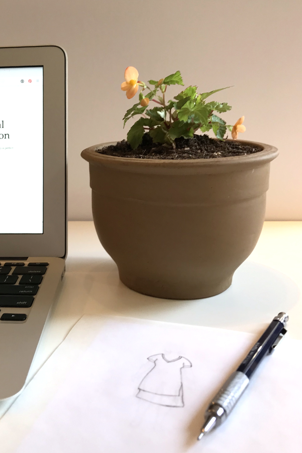 A small potted plant with orange flowers (Begonia sutherlandii) sits on a desk next to an open laptop, a pencil, and a fashion sketch of a dress.